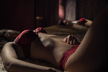 A young woman in red lace underwear caresses herself on the bed