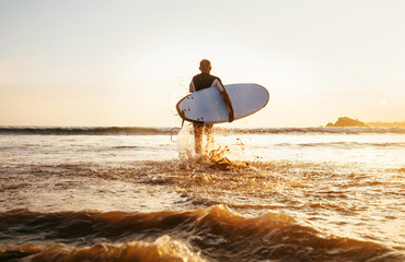 Surfer runs with surfboard towards ocean waves ta sunset time