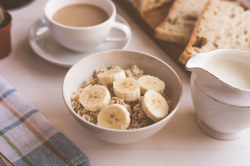 Oatmeal with a banana and coffee with milk for breakfast - close-up, on a light rustic background