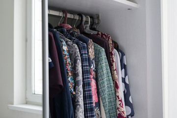 women's clothes hanging in open white cabinet