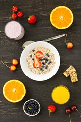Healthy breakfast of muesli, berries with yogurt and orange juice on dark background.