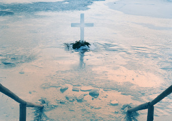Orthodox cross in iced lake with frozen Epiphany font. Winter landscape in sunset sun. Toned