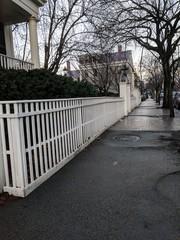 white fence on brick sidewalk