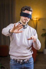 Blindfolded young man at home in living room cannot see, trying to find his way with his hands