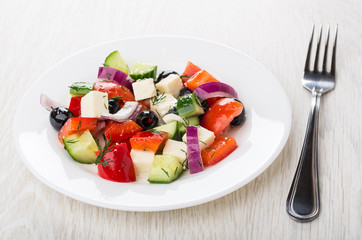 Greek salad and in white plate, and fork on table
