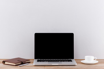 Writing book on a laptop. Clean scene of the desk in office or room. Blank screen for mock up.