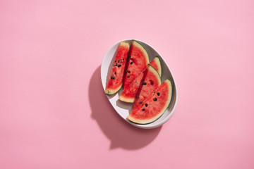 Fresh sliced watermelon in white dish on pink background.