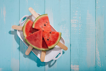 Slices of watermelon on plate on blue wooden desk.