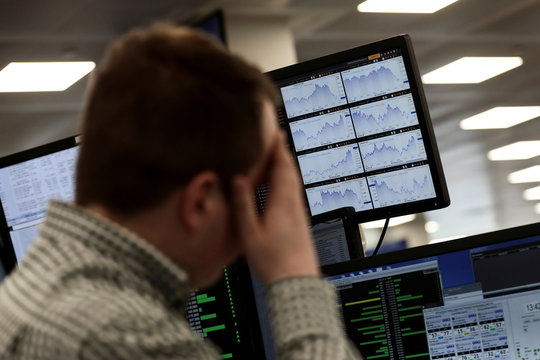Traders looks at financial information on computer screens on the IG Index the trading floor