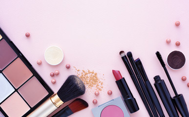 Makeup brush and decorative cosmetics on a pastel pink background with empty space. Top view