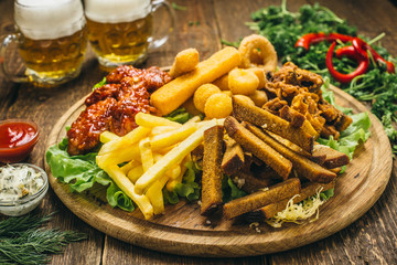 French fries,mushrooms in batter, cheese balls, cheese sticks and cheese rings in batter, on a round wooden board, with lettuce, dill, sauce, ketchup, parsley, pepper and beer