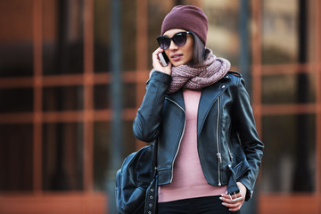 Young fashion woman in black leather jacket using cell phone in city street