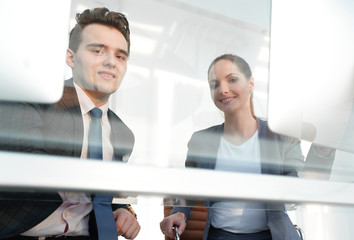 employees behind the window of a modern office