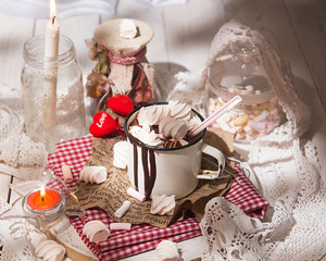Mug of hot chocolate drink with marshmallow candies on top and candles on white background. Valentin's day love concept.