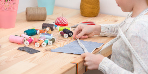 girl sews doll clothes, Child sewing