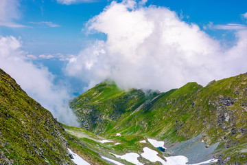 valley of Fagaras mountains in clouds. beautiful summer landscape with rocky cliffs and grassy slopes with spots of snow