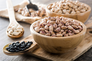 Uncooked assorted legumes in wooden bowl on wooden table