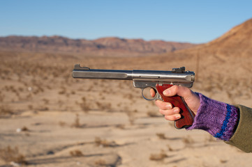 Womans hand holding and aiming target pistol in a desert setting