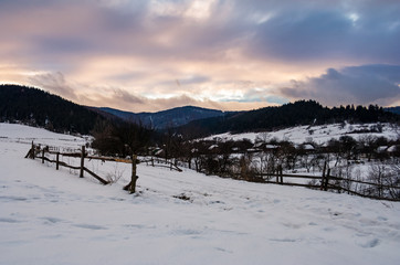 wooden fence along the snowy road. beautiful winter landscape of mountainous rural area at cloudy sunset