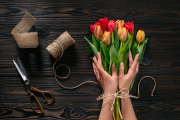 partial view of female hands, rope, scissors and bouquet of flowers on wooden surface