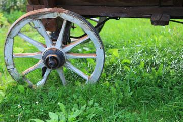 Wheel of old wagon rides around village green grass meadow.
