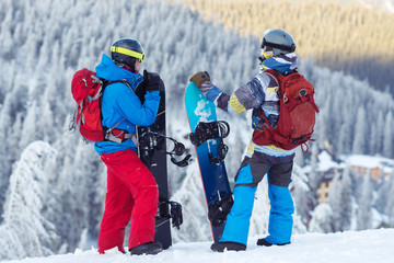 Two snowboarders, with backpacks, stand on the mountain slope
