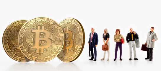 A group of people pose next to bitcoins, isolated on a white background