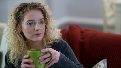Attractive blonde woman sitting with green coffee cup looking to the right