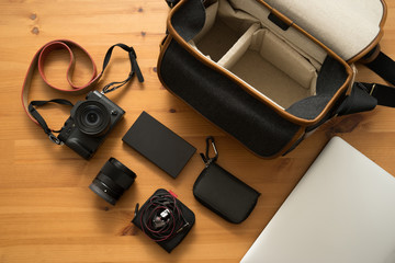 Black digital camera with orange leather strap.