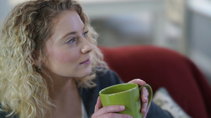 Beautiful blonde woman sitting with green coffee cup