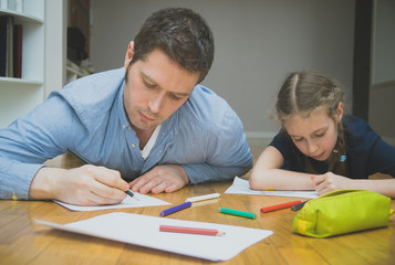 Father and her daughter drawing on the floor.