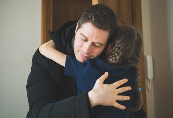 Father hugging her daughter after long trip.