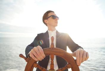 Captain. Businessman holding hand on ship rudder.