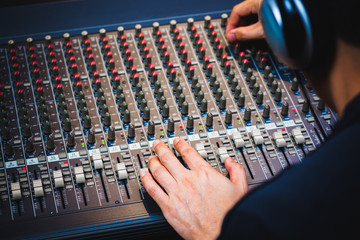 male sound engineer hands working on audio mixing console. music background