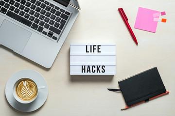 Life hacks written on lightbox in office as flatlay