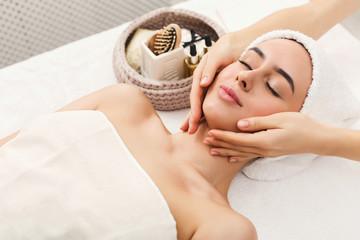 Woman getting professional facial massage at spa salon