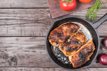 Roasted chicken pieces in cast iron pan top view with copy space