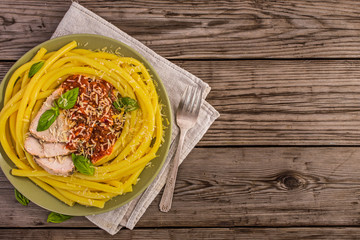 Long macaroni italian noodle pasta with pork and sauce on old wooden table with copy space