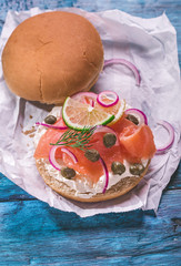 Burger with cream cheese, smoked salmon, red onion, capers and lemon on rustic blue table