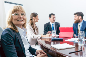 Portrait of a senior CEO or executive director wearing formal business outfits, while smiling and looking at camera with confidence during board of directors meeting in the conference room