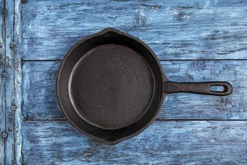 Empty iron cast pan on deep blue rustic table
