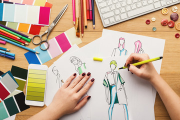 Top view on woman designer drawing clothes sketches