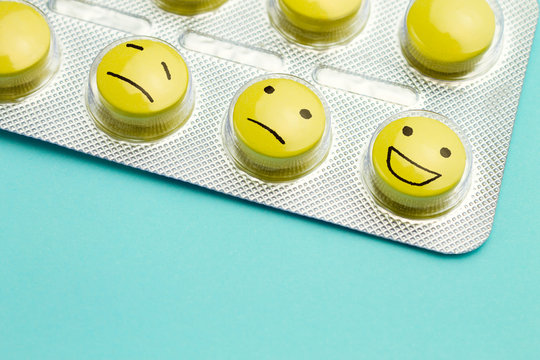 Yellow pills and funny faces in a blister on a blue background. The concept of antidepressants and healing