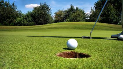 Putting Grün am Golfplatz, wo ein Golfer gerade den Ball anspricht. Golfball vor dem Loch auf einem Golfkurs mit einem Golfspieler am Ball