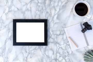 View of a marble table from above with a black empty frame, a white cup of coffee, a notebook and a ceramic cactus