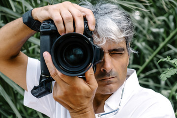 Close-up attractive white hair man making photos.