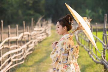 Japanese women wear kimono holding umbrellas