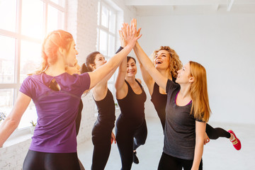 Group of five sporty ladies giving high five at gym. White loft interior. Sun glare effect. Team, friendship and helthy lifestyle concept.