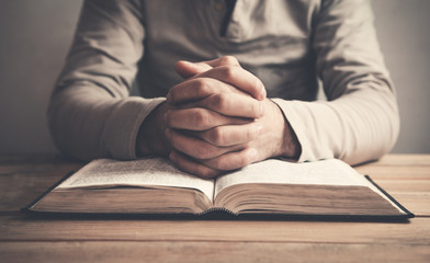 Man praying over a bible.