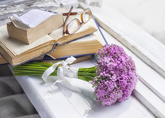 A bouquet of meadow flowers, old books and glasses on a wooden window sill.